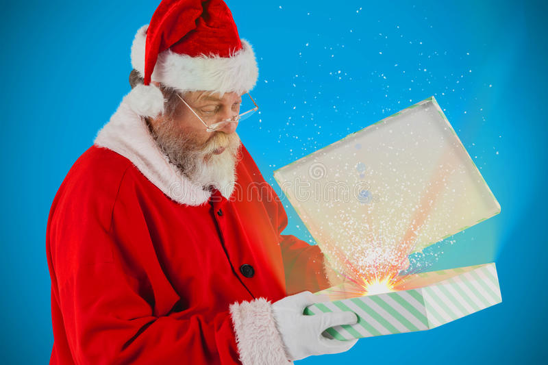 Composite image of santa claus looking at open gift box. Santa Claus looking at open gift box against blue background with vignette stock images