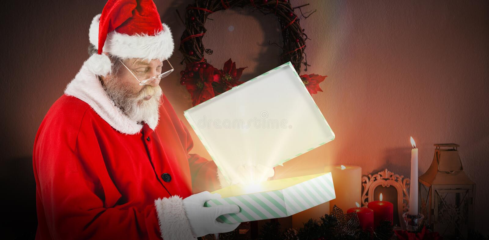 Composite image of santa claus looking at open gift box. Santa Claus looking at open gift box against candles and christmas decorations arranged on fireplace stock image