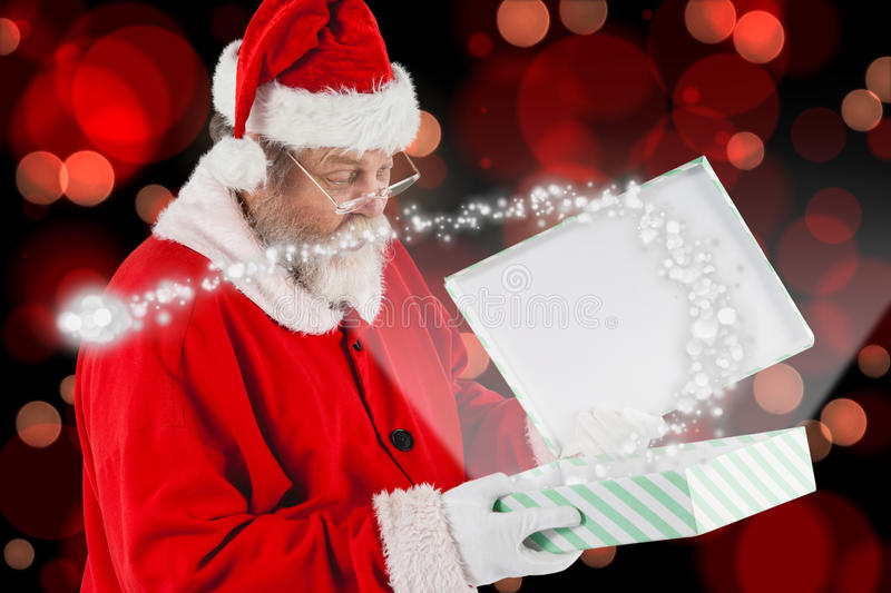 Composite image of santa claus looking at open gift box. Santa Claus looking at open gift box against red glowing dots on black stock photos