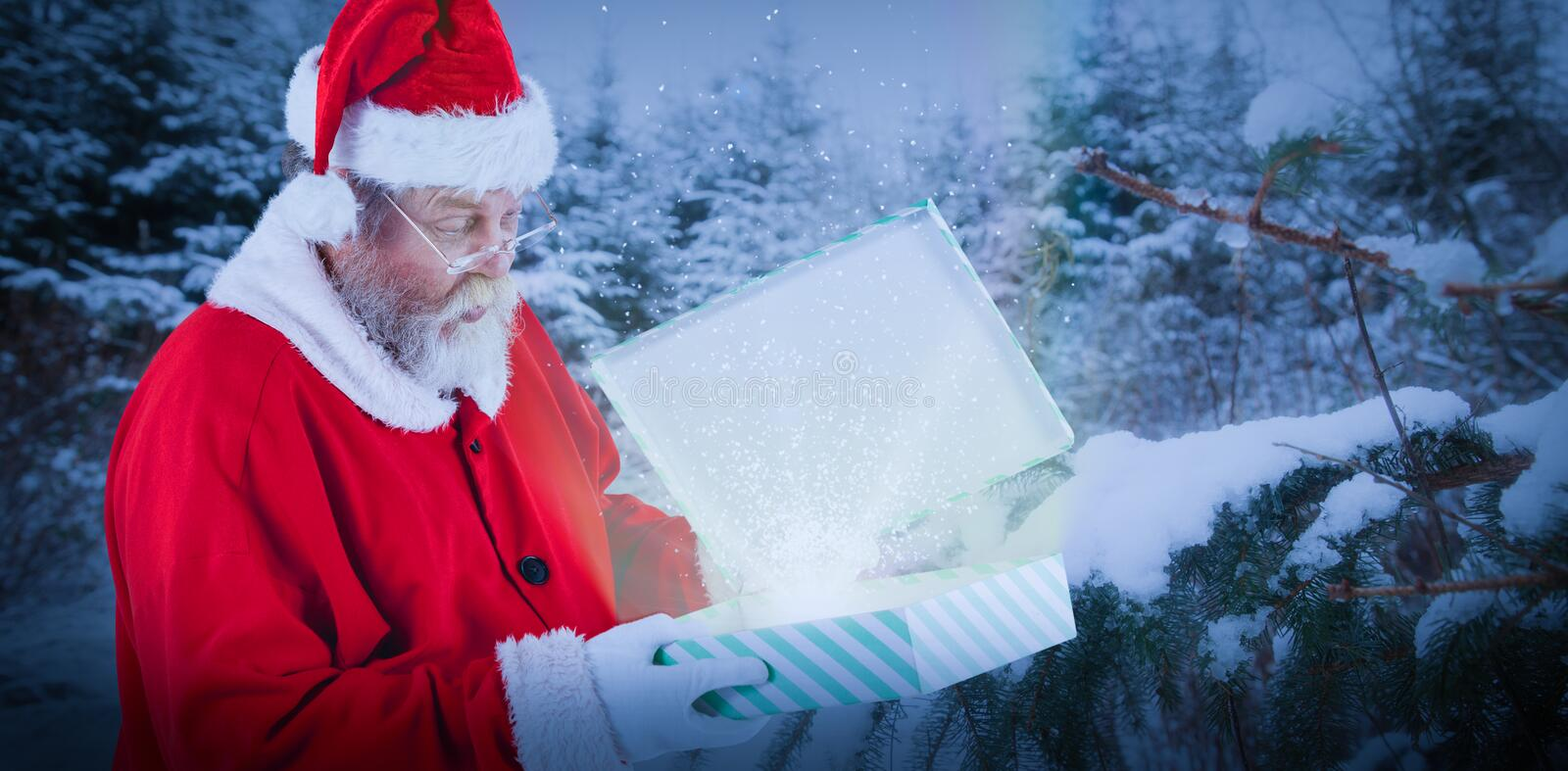 Composite image of santa claus looking at open gift box. Santa Claus looking at open gift box against snow covered trees against sky stock photos