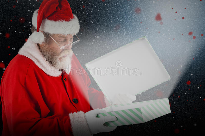 Composite image of santa claus looking at open gift box. Santa Claus looking at open gift box against snow with red flakes stock image