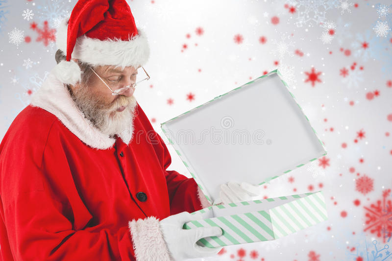 Composite image of santa claus looking at open gift box. Santa Claus looking at open gift box against snowflake pattern stock photos