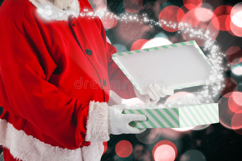 Composite image of santa claus opening gift box royalty free stock photo