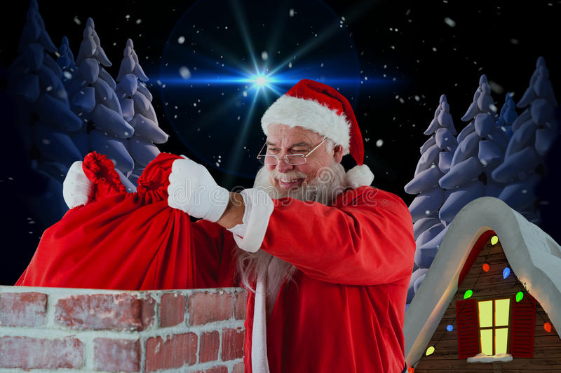 Composite image of santa claus placing christmas bag into chimney royalty free stock photo