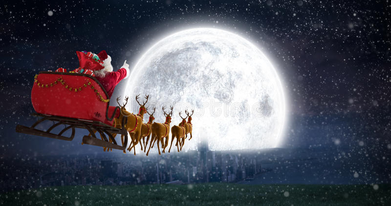 Composite image of santa claus riding on sleigh with gift box royalty free stock photography