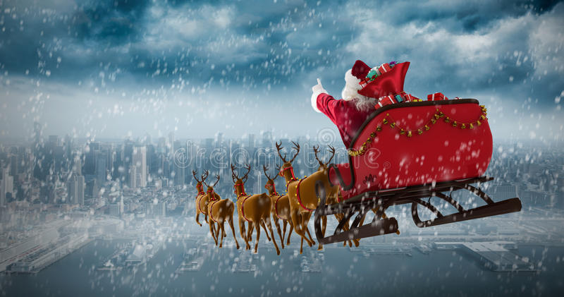 Composite image of santa claus riding on sleigh with gift box. Santa Claus riding on sleigh with gift box against coastline and city royalty free stock photo