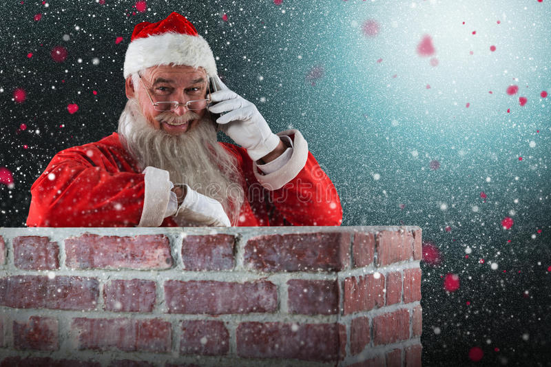 Composite image of santa claus standing beside chimney and talking on mobile phone. Santa Claus standing beside chimney and talking on mobile phone against snow royalty free stock image