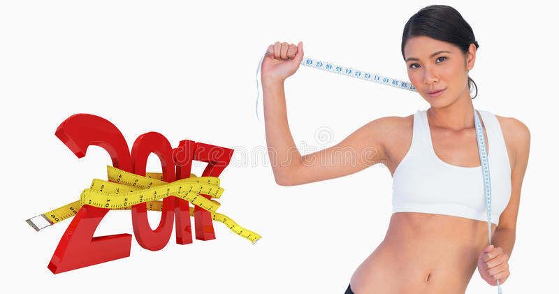 Composite image of self confident slim woman holding her measuring tape royalty free stock images