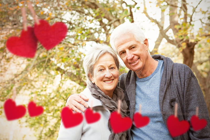 Composite image of senior couple in the park royalty free stock photography