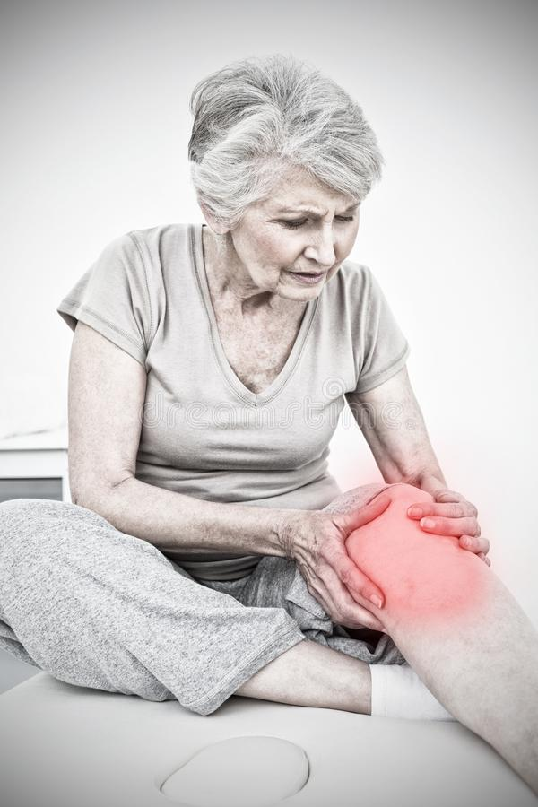 Composite image of senior woman with her hands on a painful knee. Senior woman with her hands on a painful knee against highlighted pain royalty free stock images