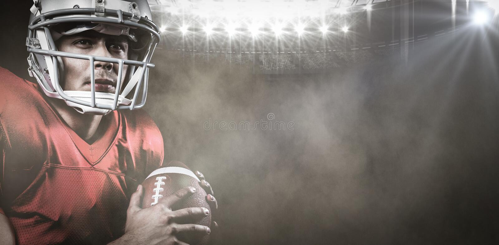 Composite image of serious american football player looking away while holding ball royalty free stock photography