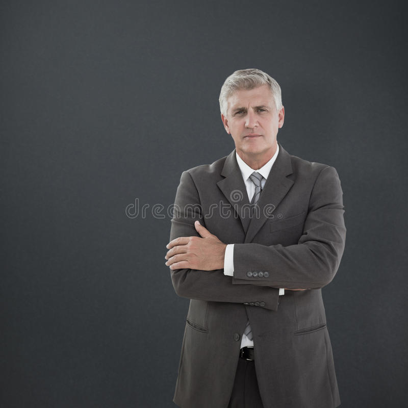 Composite image of serious businessman. Serious businessman against grey background royalty free stock images