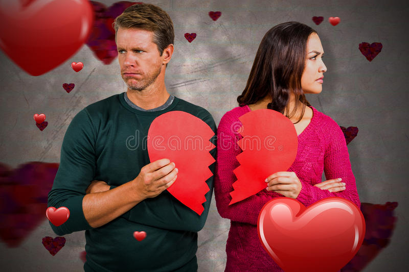 Composite image of serious couple holding cracked heart shape 3d. Serious couple holding cracked heart shape against love heart pattern 3d royalty free stock images