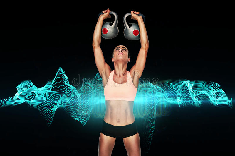 Composite image of serious female crossfitter lifting kettlebells above head royalty free illustration