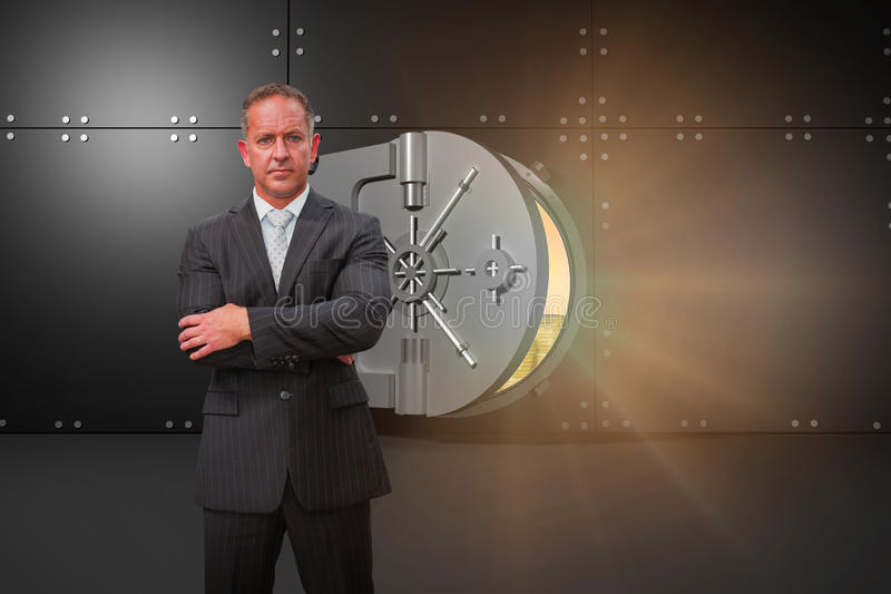 Composite image of serious manager with arms crossed in warehouse royalty free stock photography