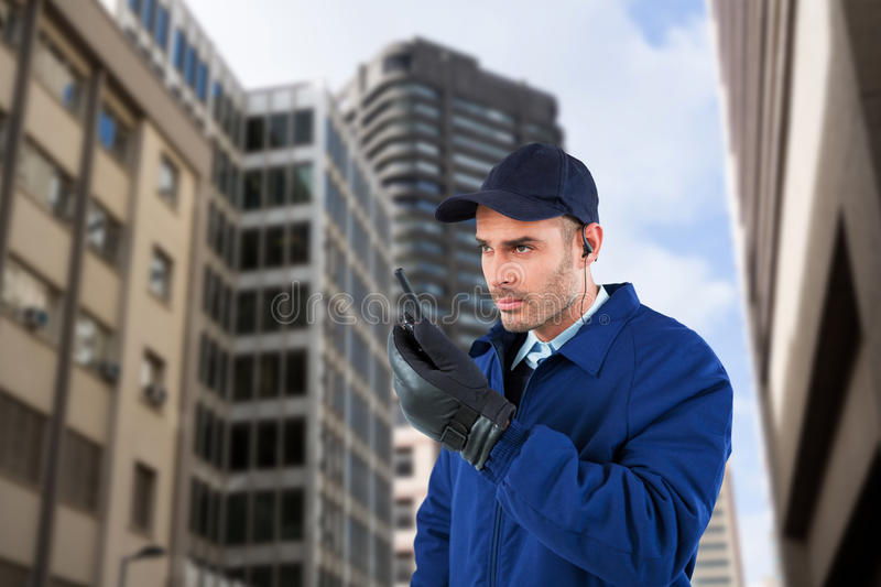 Composite image of serious security officer talking on walkie talkie. Serious security officer talking on walkie talkie against view of tall buildings stock photography
