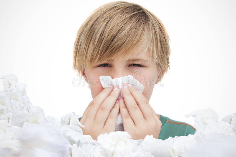 Composite image of sick little boy with a handkerchief royalty free stock image