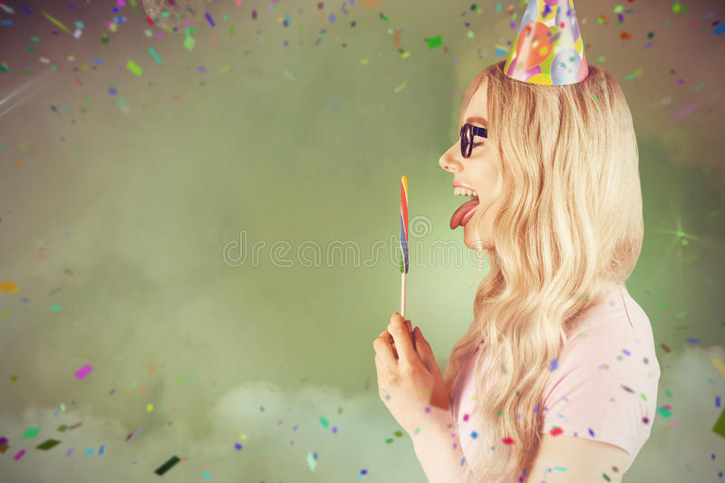 Composite image of side view of a beautiful hipster holding a giant lollipop stock photo