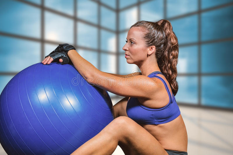 Composite image of side view of sporty woman with exercise ball stock photo