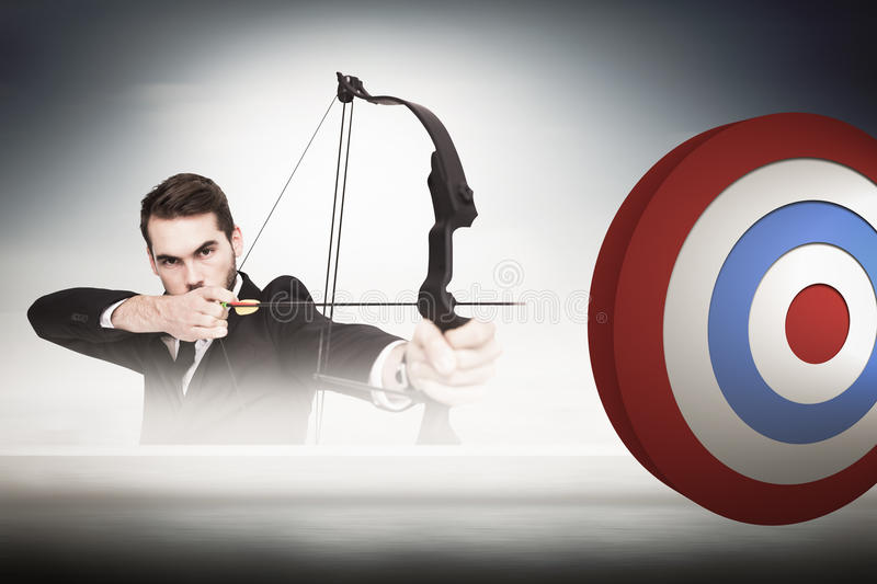 Composite image of smart businessman practicing archery looking at camera royalty free stock photos