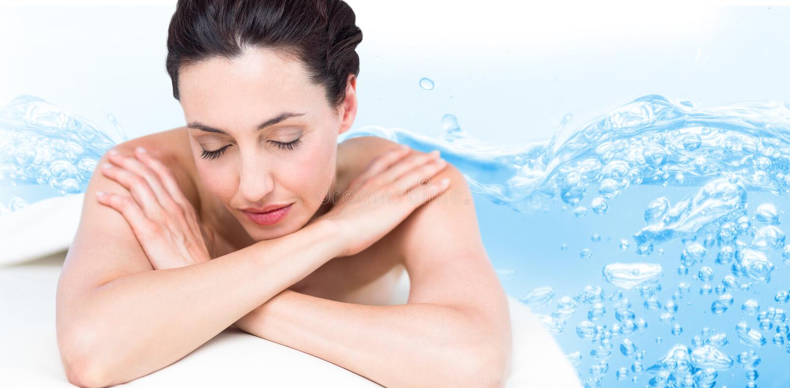 Composite image of smiling brunette relaxing on massage table royalty free stock photos