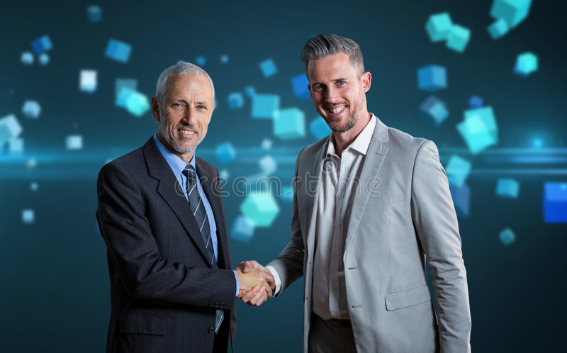 Composite image of smiling business partners shaking hands royalty free stock photo
