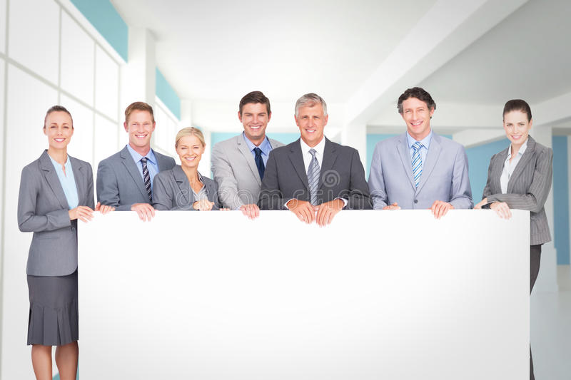 Composite image of smiling business team holding poster. Smiling business team holding poster against modern blue and white room royalty free stock photo