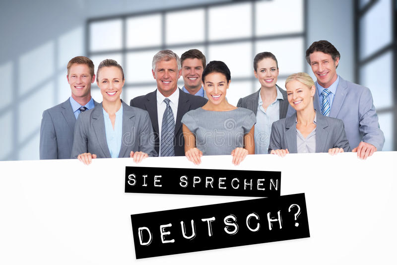 Composite image of smiling business team holding poster. Smiling business team holding poster against room with large windows showing city royalty free stock images