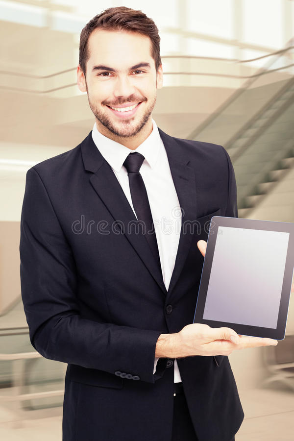 Composite image of smiling businessman showing his tablet pc. Smiling businessman showing his tablet pc against airport terminal stock image