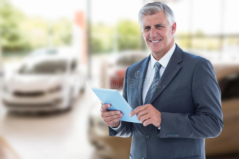Composite image of smiling businessman using his tablet. Smiling businessman using his tablet against view of row new car stock photos