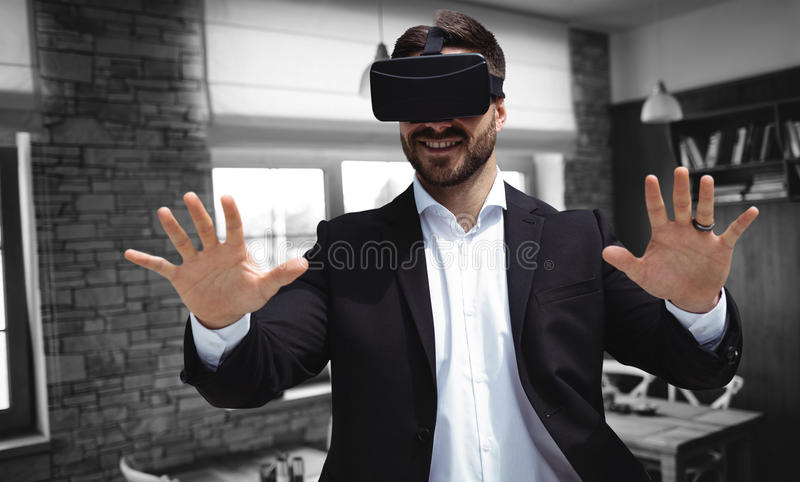 Composite image of smiling businessman using virtual reality glasses royalty free stock photo