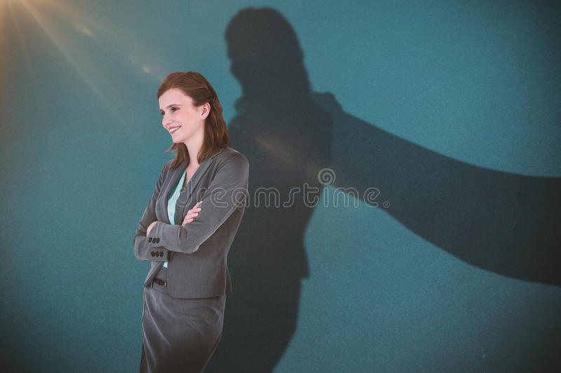 Composite image of smiling businesswoman with arms crossed. Smiling businesswoman with arms crossed against blue stock images