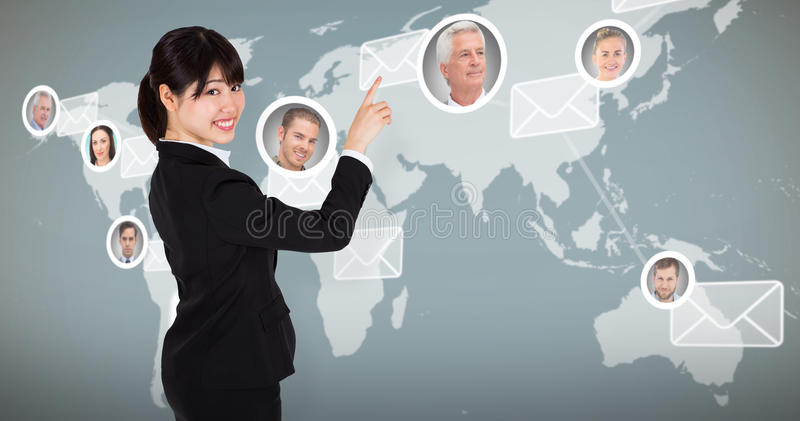 Composite image of smiling businesswoman pointing. Smiling businesswoman pointing against map with emails stock photography