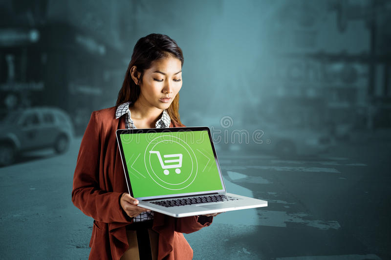 Composite image of smiling businesswoman showing a laptop. Smiling businesswoman showing a laptop against blurry new york street stock image