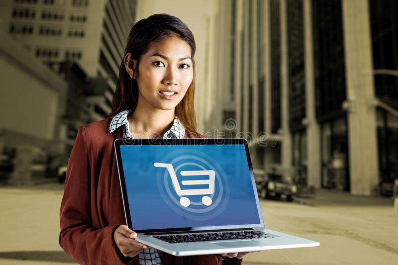 Composite image of smiling businesswoman showing a laptop royalty free stock photo