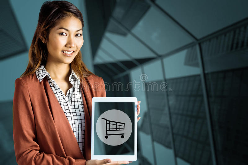 Composite image of smiling businesswoman showing a tablet royalty free stock image