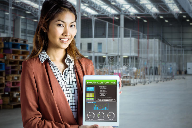 Composite image of smiling businesswoman showing a tablet stock image