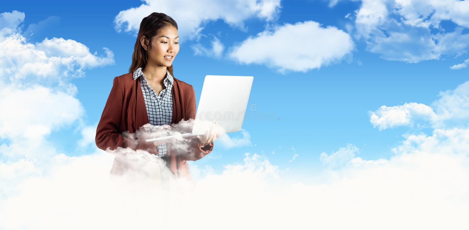 Composite image of smiling businesswoman using laptop royalty free stock image