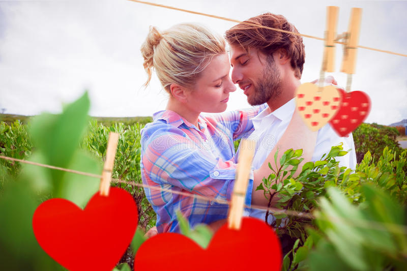 Composite image of smiling couple embracing outside among the bushes. Smiling couple embracing outside among the bushes against hearts hanging on the line stock illustration
