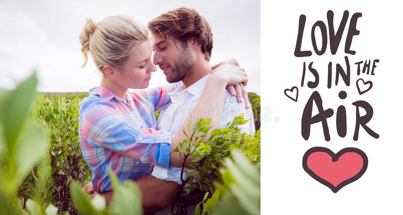 Composite image of smiling couple embracing outside among the bushes. Smiling couple embracing outside among the bushes against love is in the air royalty free illustration