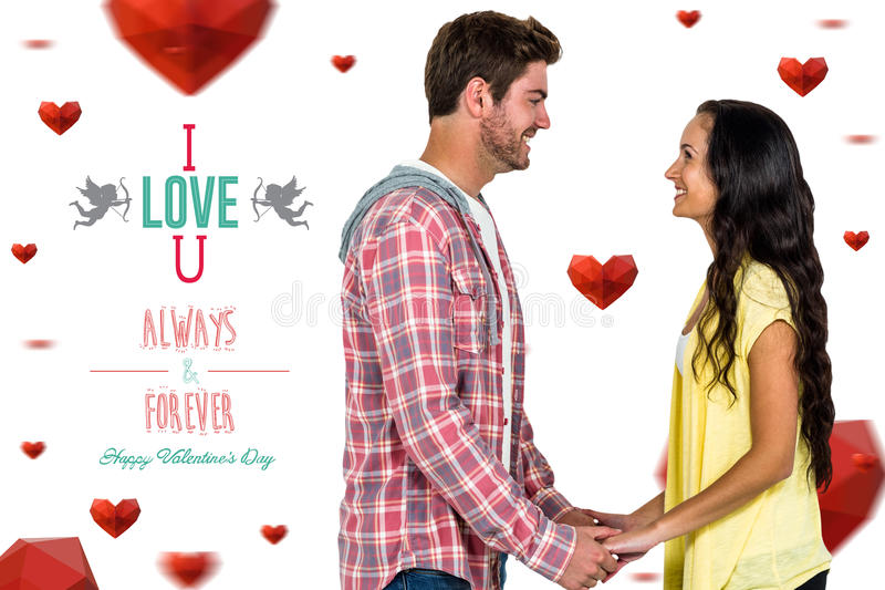 Composite image of smiling couple holding hands and looking at each other royalty free stock image