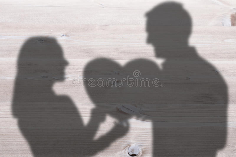 Composite image of smiling couple holding heart shape paper stock photography