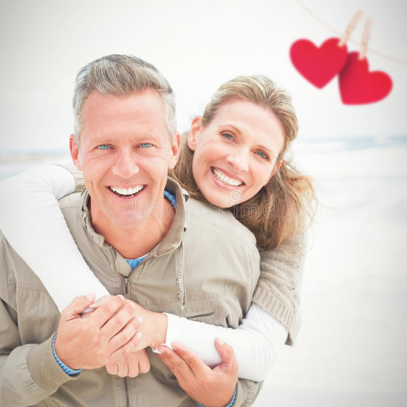 Composite image of smiling couple holding one another. Smiling couple holding one another against hearts hanging on a line stock photo