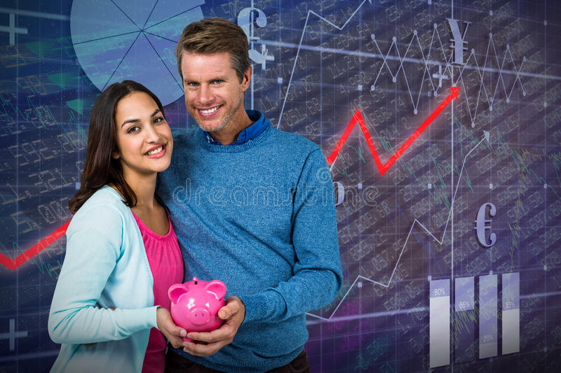 Composite image of smiling couple holding piggy bank stock images