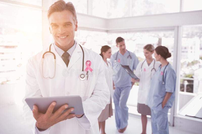 Composite image of smiling doctor holding digital tablet royalty free stock photography