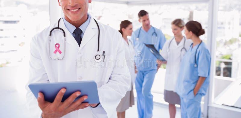 Composite image of smiling doctor holding digital tablet stock image