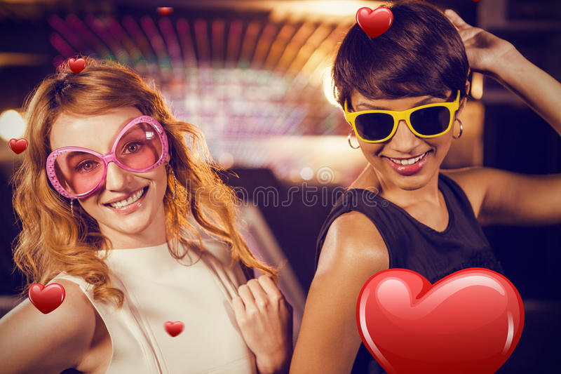 Composite image of smiling female friends dancing on dance floor. Smiling female friends dancing on dance floor against hearts royalty free stock image