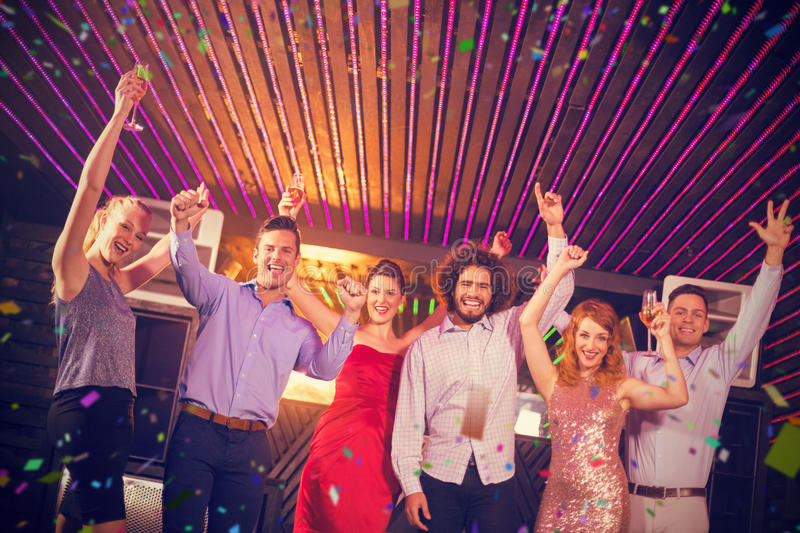 Composite image of smiling friends dancing on dance floor. Smiling friends dancing on dance floor against flying colours royalty free stock image