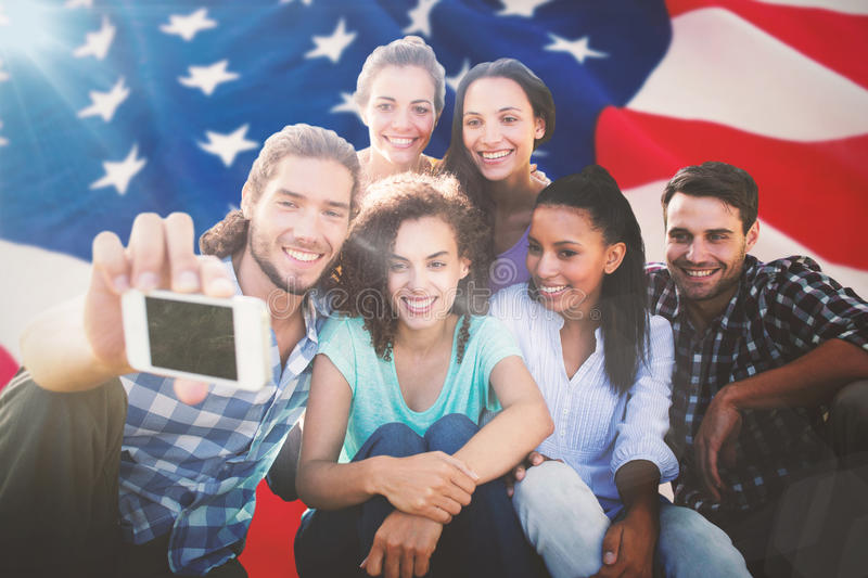 Composite image of smiling friends using media devices royalty free stock photos
