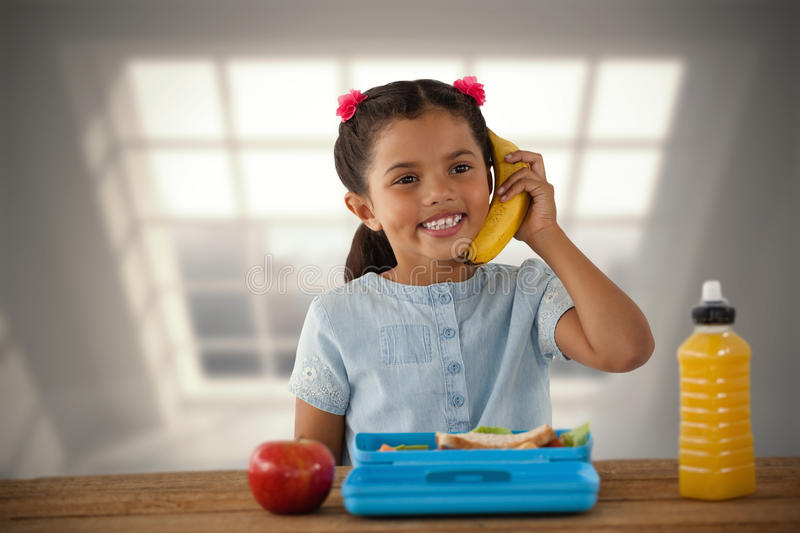 Composite image of smiling girl using banana as phone stock photography